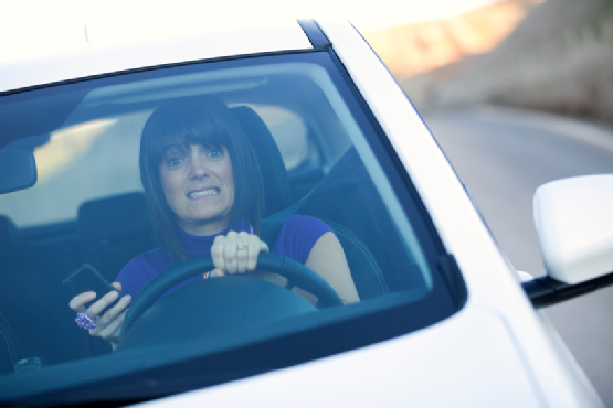 Woman driving holding a cellphone